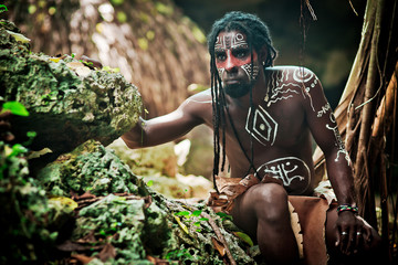 Black man with dreadlocks in the image of the Taino Indian in habitat, body painting Taino symbols