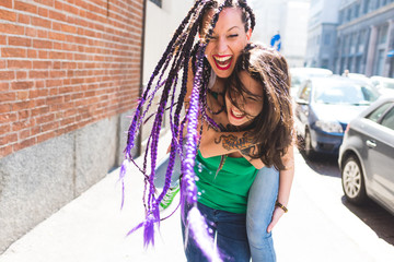 Women on city break playing piggyback in street, Milan, Italy