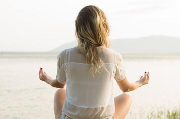 Jovem mulher meditando em posição de lótus, de frente para a água, mar, lago.