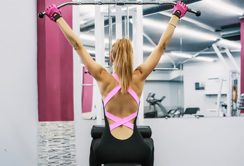 Rear view of woman using gym equipment