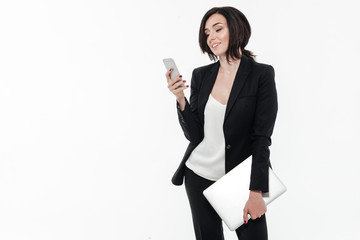 Portrait of a young attractive businesswoman in a suit typing