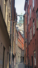 Narrow colorful street in Gamla Stan and tower of the church St. Nicholas (Storkyrkan), sunny day, Stockholm, Sweden