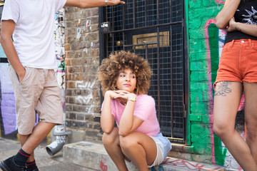 Three friends hanging out in street, young woman sitting in doorway