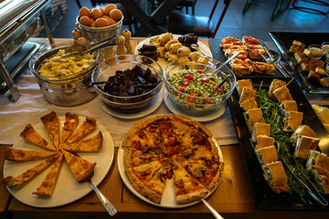Greek breakfast buffet table full with varieties of pizza, pies, pasta, beetroot, couscous salads, boiled eggs, local dishes, etc.