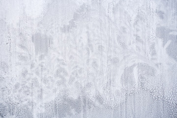 Texture of frozen snow on window glass in form of fantastic plants.