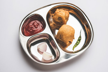 Aloo Bonda, Batata Vada or Alubonda - Indian deep fried junk but tasty food or snacks served in stainless steel plate over white background with tomato ketchup and green fried chilly