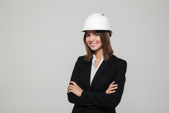 Portrait of a happy woman in hard hat and suit