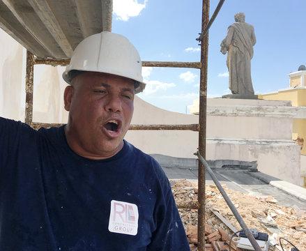 Jesus Santos sings operatic love songs while repairing plaster to a Hurricane Maria damaged facade at Cathedral of San Juan Bautista