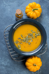 Plate of pumpkin soup with addition of pumpkin seeds and spices, high angle view, vertical shot