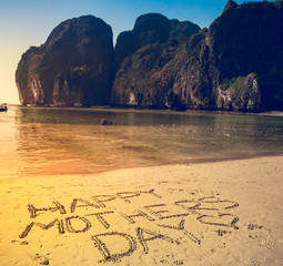 Happy Mother's Day written on the sand on a flat yellow beach. Mountains and clear ocean in the...