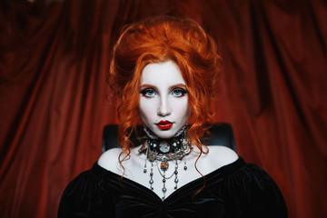 A woman is a vampire with pale skin and red hair in a black dress and a necklace on her neck. Girl witch with vampire claws and red lips. Gothic look. Outfit for halloween.