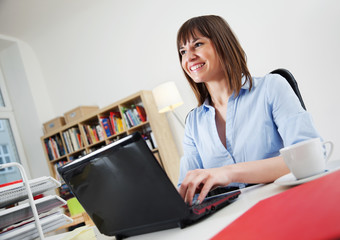 Beautiful young Woman in her Home Office working on a small Laptop Netbook