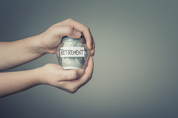 Retirement saving concept. Man hands with glass jar full of US dollars.