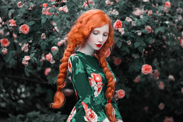 Red-haired girl with long braids in a floral dress against the background of a large bush of roses. Woman posing in the garden.