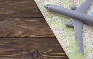 A miniature of a passenger aircraft flying on a map. A conceptual image for tourism and travel. place for text
