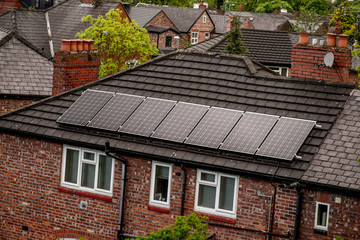 Renewable clean green energy saving efficient photovoltaic solar panels on multiple gable suburban house roof over blue sky. Manchester England