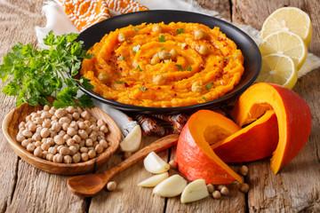 Vegetarian food: hummus with pumpkin and ingredients close-up. horizontal