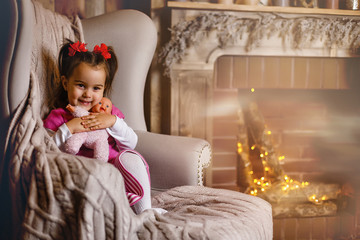 A very excited young girl sits backwards in a chair on Christmas morning. She is eager to get through breakfast and open gifts. She is wearing a Santa dress and a silver bow on her head.