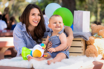 Beautiful mother with baby infant child with big gorgeous smile and adorable expression at family gathering