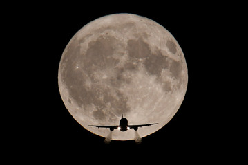 A passenger plane, with a full Harvest moon seen behind, makes its final landing approach towards Heathrow Airport in London, Britain