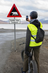 A teen boy taking picture of a polar bear warning sign in Svalbard