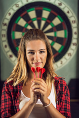 Portrait of happy woman playing darts