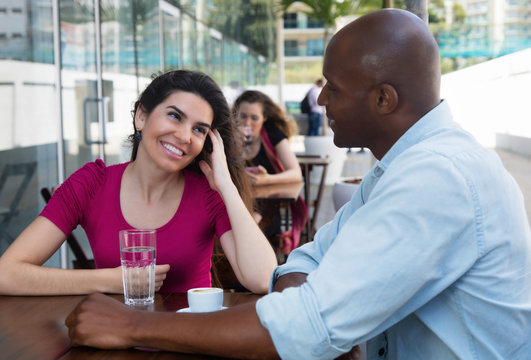 Caucasian woman flirting with african american man at restaurant