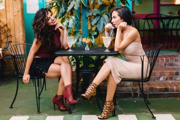 Two woman friends having cocktails at an outdoor mexican patio restaurant
