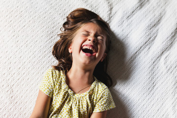 Young girl laying down laughing