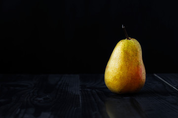 Yellow pear on a black background and a wooden table