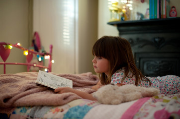 Girl laying on her bed reading