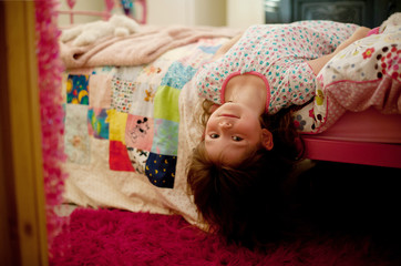 Little girl hanging upside down off the side of her bed