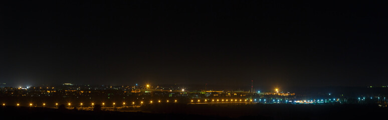 The bright lights of the city streets in the background of the night sky. Panoramic view of residential areas.