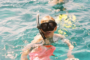 Teenage boy in the ocean wearing a mask and snorkel