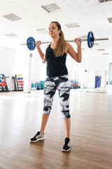 girl trains with a barbell in the gym