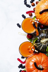 Fresh pumpkin juice on a white Halloween background with black candy, top view
