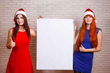 Two beautiful smiling women in Santa caps with thumb up gesture and big empty board in hands. Free space for advertisement or text, mockup for design.New Year, Christmas time sales concept