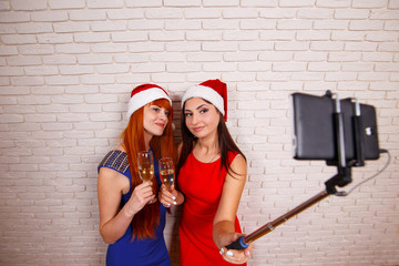 Young beautiful women in Santa caps having fun, drinking champagne, taking self portrait with a smartphone and selfie stick. Free space for text design.New Year, Christmas, party, technology concept