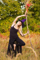 Active female in witch costume practicing yoga