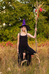 Blonde female in witch costume practicing yoga