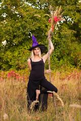 Joyful female in witch costume practicing yoga