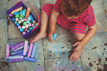 A young boy drawing with chalk.