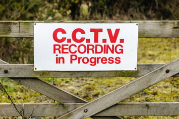 Sign on a wooden gate advising public that CCTV recording is in progress