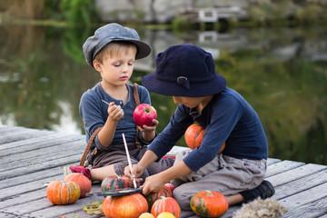 Cheerful kids paint small Halloween pumpkins