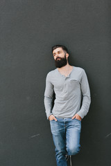 Handsome young bearded man leaning against a wall