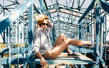 Sensual young woman in urban outfit enjoyiing sun on metal construcion.