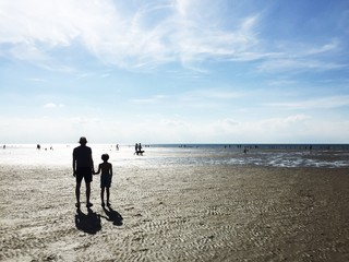 Silhouettes of father and son at the beach