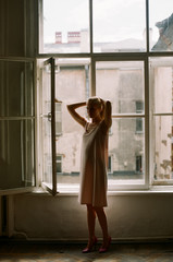 Young woman standing against window