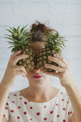 Pineapple face: beautiful young woman hides her eyes behind mini pineapples