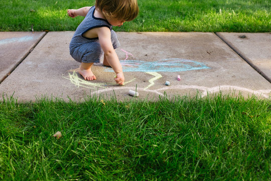 A young boy draws with chalks outside in the summer.